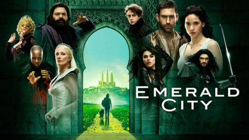 "An assortment of characters arrayed in front of a gate. The doorway in the middle of the gate opens onto a yellow brick road, where we see Dorothy and a dog walking into the distance. Words read ""Emerald City."""