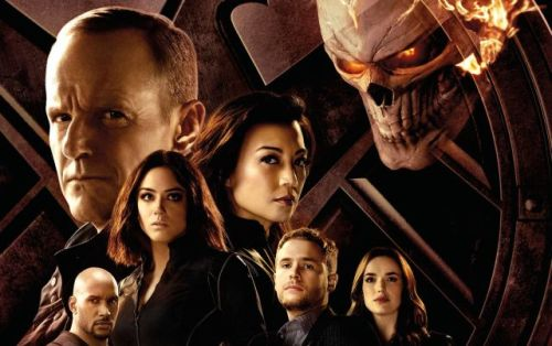 The cast of Agents of SHIELD standing in front of a SHIELD logo, including Coulson, May, Daisy, Mack, Fitz, and Simmons. The flaming skull of Ghost Rider looms over them.