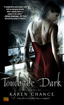 "A woman with a star symbol tattooed on her back, standing near an office widow. The words in front of her read ""Touch the Dark, Karen Chance, Can you ever really trust a vampire?"""