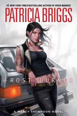 "A woman leaning against the back of a car. The words read ""#1 New York Times Bestselling Author of River Marked, Patricia Briggs, Frost Burned, a Mercy Thompson novel."""