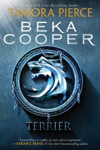 "An image of a pendent, with a creature's head on it, with the words ""#1 New York Times Bestsellling Author Tamora Pierce, Beka Cooper, Terrier, 'Tamora Pierce is a pillar, an icon, and an inspiriation.' - Sarah J. Maas, #1 New York Times bestselling author"""