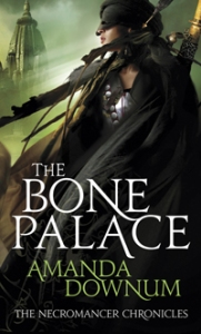 """A masked figure stands before a spire. The words read """"The Bone Palace, Amanda Downum, The Necromancer Chronicles""""."""